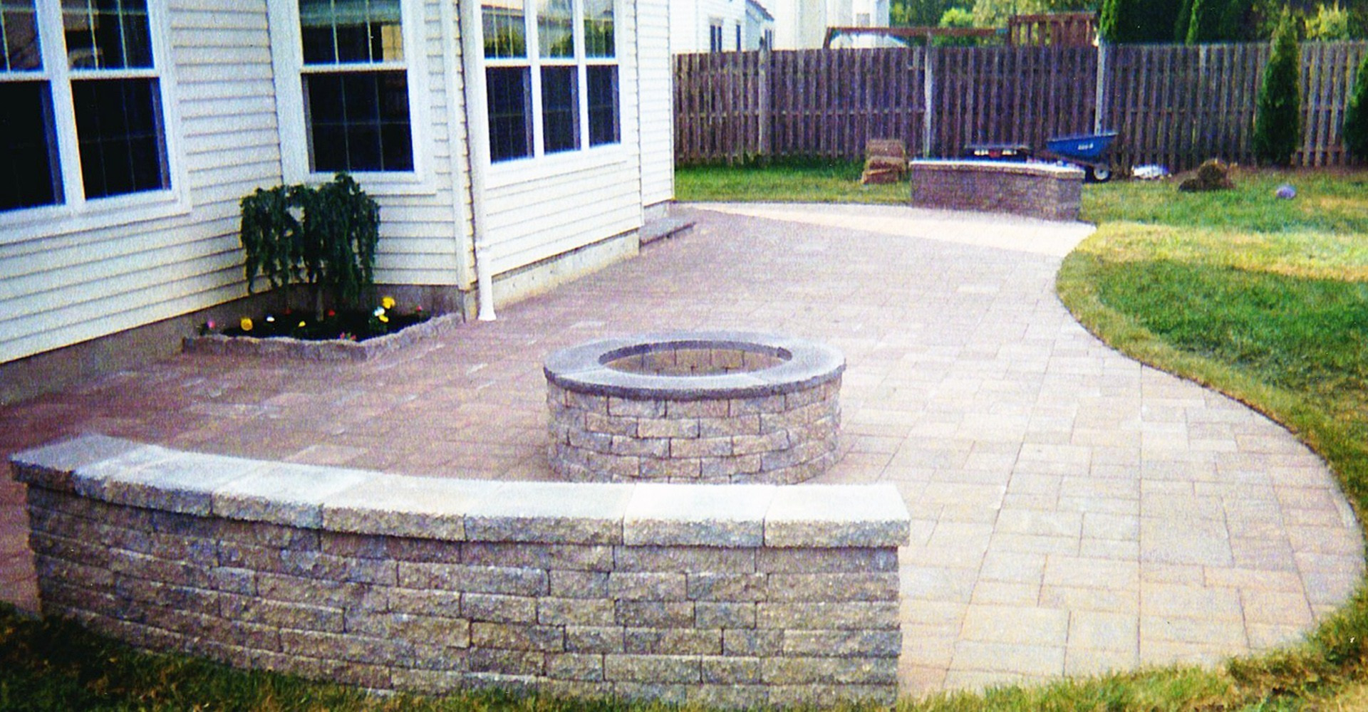 paver patio with firepit and partial wall
